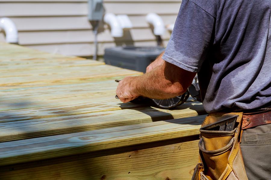Backyard Deck Reconstruction handsome man carpenter installing wood floor terrace outdoor in new house construction